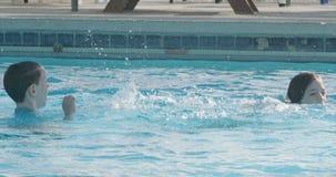 As crianças que saltam e que jogam em uma piscina filme