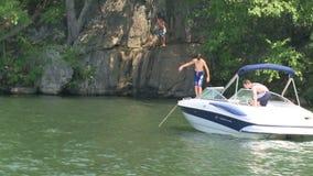 As crianças que saltam fora de um barco de motor amarrado e que balançam em uma corda fora de um penhasco filme