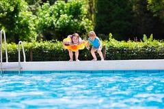 As crianças que saltam na piscina Fotos de Stock