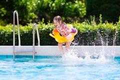 As crianças que saltam na piscina Fotografia de Stock