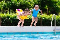 As crianças que saltam na piscina Fotografia de Stock Royalty Free