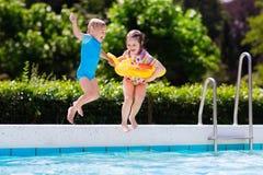 As crianças que saltam na piscina Imagem de Stock Royalty Free