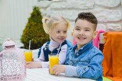 As crianças que têm as crianças saudáveis do café da manhã que bebem sucos e têm o divertimento Imagem de Stock
