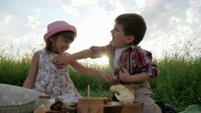 As crianças que têm o divertimento no ar fresco, criança no piquenique, família que descansa na natureza, amigos riem felizmente, filme