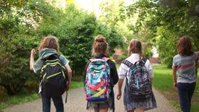 As crianças retornam da escola, jogam acima os papéis, último dia do estudo, começo dos feriados, vista traseira filme