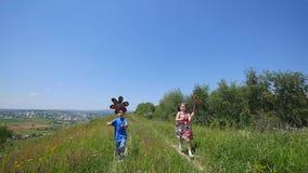 As crianças são jogadas com uma turbina eólica Girândola colorido das crianças que gira no vento Na perspectiva de filme