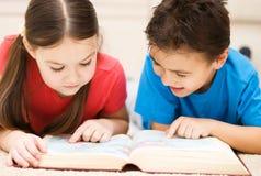 As crianças são livro de leitura Foto de Stock