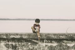 As crianças sós decolam as sapatas e está sentando-se na terra fotografia de stock
