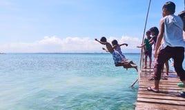 As crianças saltam em pares em um passadiço em um recurso em Olango, tomado em março de 2018 Foto de Stock Royalty Free