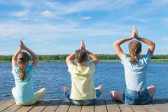 As crianças sentam-se no cais, em uma pose da ioga, fora fotografia de stock
