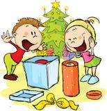 As crianças sob a árvore de Natal desempacotam presentes Fotografia de Stock