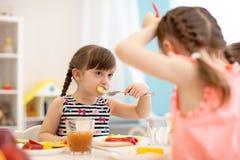 As crianças têm o almoço na guarda, no jardim de infância ou na casa fotografia de stock