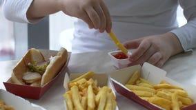 As crianças têm o almoço no café do fast food Os meninos bebem a limonada e comem Hamburger no fundo do parque de estacionamento  vídeos de arquivo