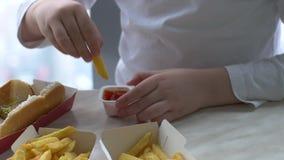 As crianças têm o almoço no café do fast food Os meninos bebem a limonada e comem Hamburger no fundo do parque de estacionamento  video estoque