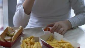 As crianças têm o almoço no café do fast food Os meninos bebem a limonada e comem Hamburger no fundo do parque de estacionamento  filme