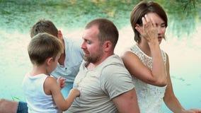 As crianças têm o divertimento junto com pais Um photoshoot no banco de uma lagoa toda a família A família grande bonita tem um r filme