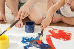 As crianças tiram cores brilhantes no papel, sentando-se no assoalho imagem de stock