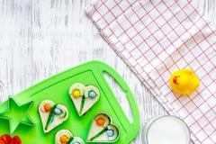As crianças tomam o café da manhã com os sanduíches engraçados no copyspace de madeira claro da opinião superior do fundo da tabe Foto de Stock
