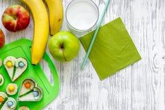 As crianças tomam o café da manhã com sanduíches e frutos engraçados no copyspace de madeira claro da opinião superior do fundo d Imagem de Stock Royalty Free