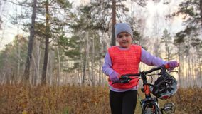As crianças uma caucasianos andam com a bicicleta no parque do outono A menina que anda o ciclo alaranjado preto na criança da fl vídeos de arquivo