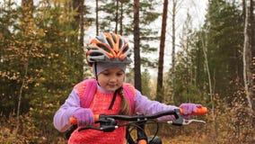 As crianças uma caucasianos andam com a bicicleta no parque do outono A menina que anda o ciclo alaranjado preto na criança da fl filme