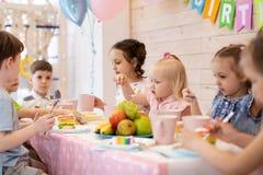 As crian?as comem o bolo na festa de anos fotos de stock royalty free