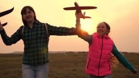 as crian?as jogam o avi?o do brinquedo Os adolescentes querem transformar-se piloto e astronauta As meninas felizes correm com pl video estoque