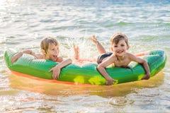 As crian?as nadam no mar em um colch?o infl?vel e para ter o divertimento foto de stock royalty free