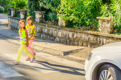 As crianças da escola primária estão cruzando a rua Imagens de Stock Royalty Free