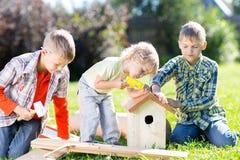 As crianças entregam o trabalho junto no gramado no verão Fotos de Stock Royalty Free
