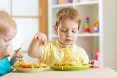 As crianças prées-escolar comem o alimento saudável no jardim de infância Foto de Stock