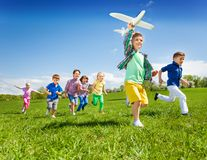 As crianças running ativas com o menino que guarda o avião brincam Fotografia de Stock Royalty Free