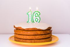As décimas sextas velas do aniversário na baunilha mergulhada rústica do vegetariano endurecem imagem de stock royalty free
