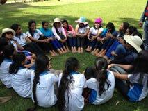 As dúzias bonitas das meninas estão sentando-se em um círculo fotografia de stock royalty free