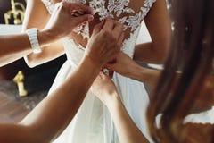 As damas de honra amarram uma curva no vestido de casamento fotografia de stock