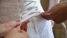 As damas de honra apertaram o vestido de casamento do espartilho filme