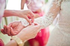 As damas de honra bonitas que amarram nós no ` s da noiva cuffs antes de seu weddi imagem de stock