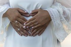 As damas de honra estão guardando as mãos em sua cerimônia de casamento anéis e anéis dos noivos Fotos de Stock Royalty Free