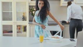 As danças da mulher na cozinha durante sua amiga estão cozinhando video estoque