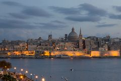 Malta - Lights of Valletta from Sliema at dusk. As daylight fades, the lights of Malta`s capital Valletta, shine across the harbor towards Sliema Stock Image
