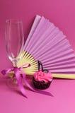 As decorações cor-de-rosa do partido com fã, vidro do champanhe e salto alto calçam o queque - vertical. Foto de Stock Royalty Free