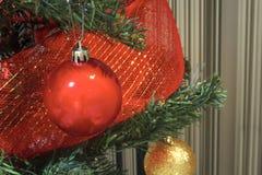 As decorações do Feliz Natal cardam bolas e fitas das quinquilharias em uma árvore foto de stock