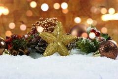 As decorações do Natal e a estrela glittery aninharam-se na neve com bok fotografia de stock