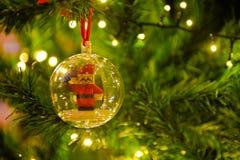 As decorações do Natal, Santa Claus dentro da bola transparente, árvore do xmas iluminam-se imagens de stock
