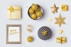 As decorações e os objetos no preto e o ouro do Natal para a zombaria acima do molde projetam Vista de acima Imagens de Stock