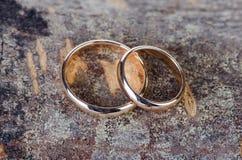 As duas alianças de casamento do ouro no fundo de madeira Foto de Stock