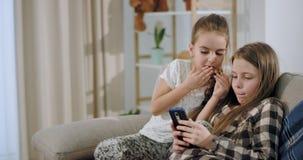 As duas irmãs atrativas bonitas que jogam um jogo usando um smartphone ao sentar-se no sofá após a escola têm um relaxamento vídeos de arquivo