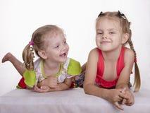 As duas meninas colocam a inclinação em suas mãos, sorrindo Fotos de Stock