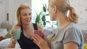 As duas meninas estão bebendo o café video estoque
