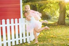 As duas meninas no campo de jogos contra o parque ou a floresta verde Fotos de Stock